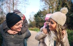 Föräldrar som på ryggen utomhus ger ritt till lyckliga barn royaltyfri foto