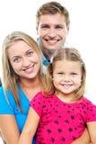 Föräldrar som poserar med den gulliga le dottern Royaltyfria Foton