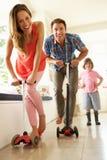 Föräldrar som rider barns sparkcyklar Arkivfoto