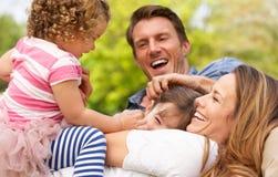 Föräldrar som sitter med barn i fält Royaltyfria Foton
