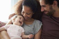 Föräldrar som sitter på det Sofa Cuddling Baby Daughter At hemmet Arkivbild