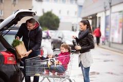 Föräldrar som skjuter shoppingvagnen med livsmedel och deras döttrar royaltyfri bild