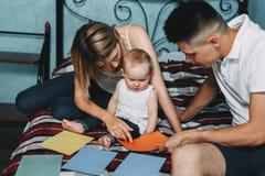 Föräldrar som spelar den framkallande leken med dottern royaltyfri fotografi