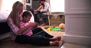 Föräldrar som spelar lekar med barn i sovrum