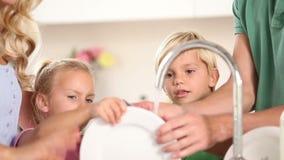Föräldrar som tvättar disk med deras barn lager videofilmer