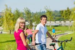 Föräldrar som tycker om att cykla Arkivfoto