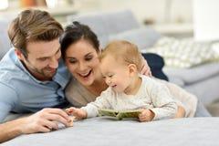 Föräldrar som tycker om med, behandla som ett barn flickan hemma royaltyfria foton