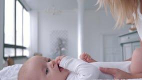 Föräldraskap som ler försiktig lek för mamman med hennes litet, behandla som ett barn flickan som ligger på ändrande tabellslut u lager videofilmer