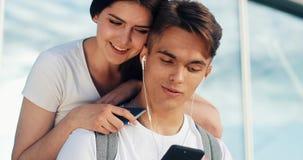 Förälskad användande smartphone för lyckliga par Ungt gift par som har gyckel, i att vänta på ett flyg på flygplatsen cambodia sk lager videofilmer