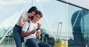 Förälskad användande smartphone för lyckliga par Ungt gift par som har gyckel, i att vänta på ett flyg på flygplatsen cambodia sk stock video
