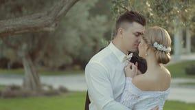 Förälskad brud och brudgum som kysser i parkera lager videofilmer