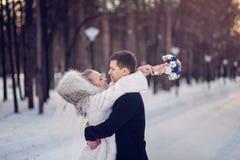 Förälskad brud- och brudgumomfamning för par i en bröllopdag i vinterskog Royaltyfri Foto