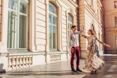 Förälskad dans för unga lyckliga par vid slotten utomhus Man och kvinna som har gyckel i stad arkivfoton