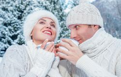 Förälskad drink för slags tvåsittssoffapåkläddpar som är varm av te i vinterskog Arkivfoton