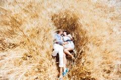 Förälskad flicka och grabben som kramar i ett fält Arkivfoton
