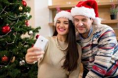 Förälskad görande selfi för par bredvid julgranen royaltyfri foto