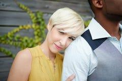 Förälskad kel för attraktiva och stilfulla mångkulturella par vid ett staket i enfylld stads- inställning Royaltyfri Foto