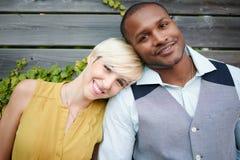 Förälskad kel för attraktiva och stilfulla mångkulturella par vid ett staket i enfylld stads- inställning Arkivfoton