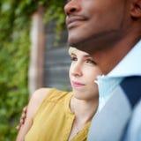 Förälskad kel för attraktiva och stilfulla mångkulturella par vid ett staket i enfylld stads- inställning Royaltyfri Bild