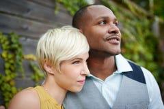 Förälskad kel för attraktiva och stilfulla mångkulturella par vid ett staket i enfylld stads- inställning Royaltyfria Bilder