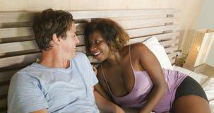 Förälskad kel för blandade etnicitetpar tillsammans hemma i säng med kvinnan och caucasianen för härlig skämtsam svart afro den a arkivbild