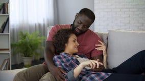 Förälskad kel för par på soffan och att tycka om mjukhet och förälskelse tillsammans, förbindelse royaltyfria foton