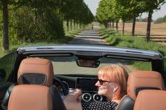 Förälskad ritt för äldre par i konvertibel bil arkivbild