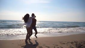 Förälskad spring för barnpar på havsstranden, mankram hans kvinna och rotering omkring Flickan hoppar in i hennes pojkvänhänder lager videofilmer