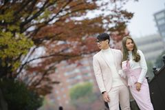 Förälskad ställning för unga japanska par tillsammans under höstträd Royaltyfria Bilder