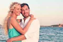 Förälskad tyckande om solnedgång för romantiska par på stranden Arkivfoto