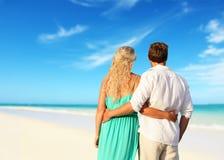 Förälskad tyckande om sommar för romantiska par på stranden Arkivbilder