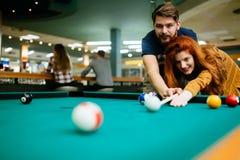 Förälskad tyckande om spela billiard för par i stång Arkivbilder