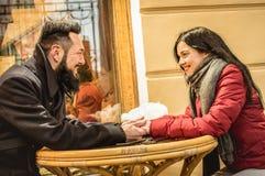 Förälskad tyckande om vintertid för lyckliga par på restaurangstången Arkivbild