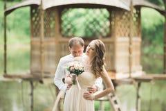 Förälskade älskvärda par kyssa sig på dagbröllopet som utomhus står i parkera nära sjön Arkivbild