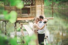 Förälskade älskvärda par kyssa sig på dagbröllopet som utomhus står i parkera nära sjön Royaltyfria Foton