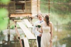 Förälskade älskvärda par kyssa sig på dagbröllopet som utomhus står i parkera nära sjön Arkivbilder