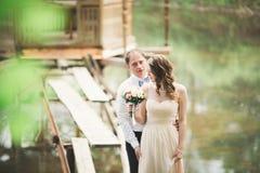 Förälskade älskvärda par kyssa sig på dagbröllopet som utomhus står i parkera nära sjön Arkivfoto