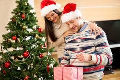 Förälskade öppningsgåvor för par nära julgranen royaltyfri fotografi
