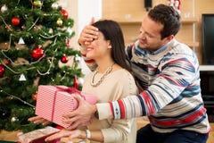 Förälskade öppningsgåvor för par nära julgranen arkivbild