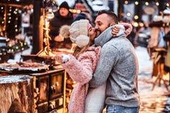 Förälskade attraktiva par och att tycka om spendera tid tillsammans, medan omfamna på vintermässan på en jultid arkivbild