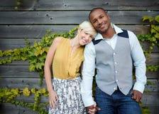 Förälskade innehavhänder för attraktiva och stilfulla mångkulturella par vid ett staket i enfylld stads- inställning Arkivbilder
