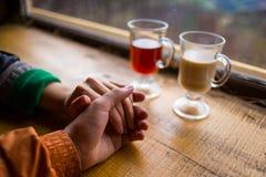 Förälskade innehavhänder för par, paren som dricker varmt kaffe och arkivfoton