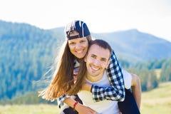 Förälskade lyckliga par går överst av berg Den unga lyckliga mannen rymmer hans flickvän royaltyfri foto