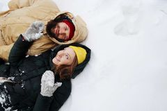Förälskade lyckliga par ha gyckel i snön arkivbilder