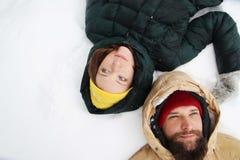Förälskade lyckliga par ha gyckel i snön fotografering för bildbyråer