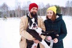 Förälskade lyckliga par ha gyckel i snön med hans behandla som ett barn hunden arkivbilder
