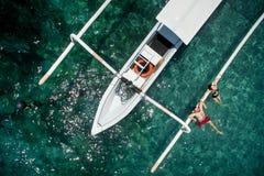 Förälskade lyckliga romantiska par kopplar av nära en yacht i havet medan bröllopsresa Arkivbild