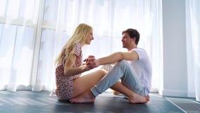 Förälskade lyckliga unga par sitter på golv- och hållhänder i solig studio lager videofilmer