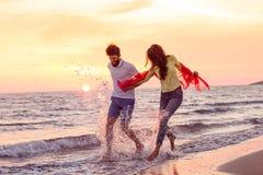 Förälskade lyckliga unga romantiska par har gyckel på den härliga stranden på den härliga sommardagen Arkivfoton