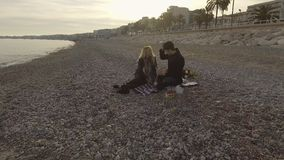 Förälskade man och kvinna ha picknicken vid sjösidan, öppnande flaska av vin, datum lager videofilmer